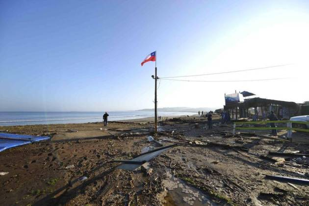 A man walks past a lone Chilean flag where surfing schools once stood, swept away by an earthquake-triggered tsunami in Concon, Chile. Courtesy Miami Herald
