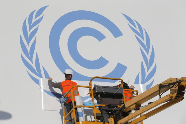 Image: Workers install a logo on the facade of the U.N Climate Conference in Le Bourget, outside Paris. Courtesy of Architect Magazine, Associated Press, photo by Christophe Ena