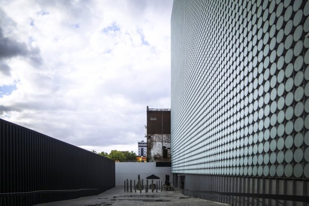 Image: RMIT University's design hub in Melbourne has an exterior made of sandblasted glass disks, which pivot through the day like vertical blinds to control interior light and heat gain. The facade changes tempo throughout the day; sometimes it's a teal grid in direct daylight, then a more delicate steel blue lace when backlit by the sun. Courtesy Tech Insider, photo by Andrew Michler