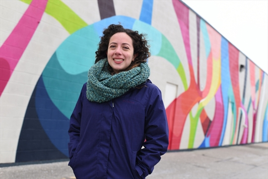Image: Stephanie Boutari next to her most recent mural on the rear wall of 800 Franklin Blvd. in Cambridge. Courtesy of Waterloo Region Record, photo by Peter Lee