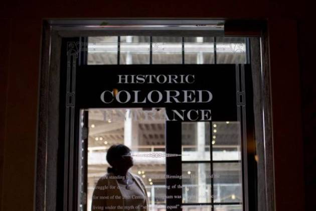Image: A woman stands in the old doorway of the Lyric Theatre, in Birmingham, Ala. Courtesy of Global News and AP, photo by Brynn Anderson